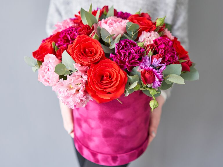 Women holding fresh red and pink flowers in a pink box