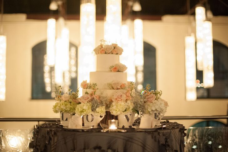 """The white wedding cake at the reception was created by Clay's Creative Corner Bakery. It was decorated with pink roses, ivory hydrangeas and baby's breath. Small flower arrangements on the cake table filled ceramic mugs that spelled out """"Love."""""""