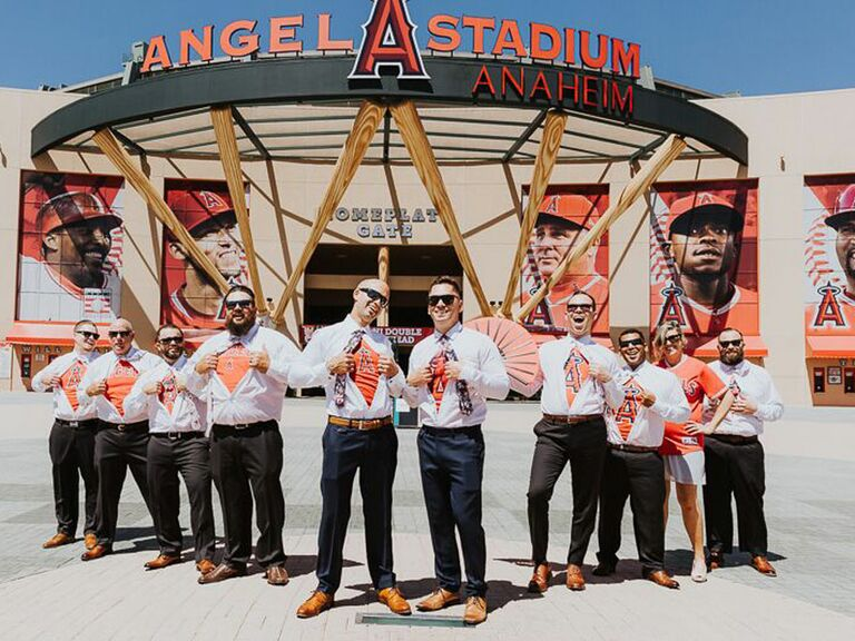 Groom and groomsmen showing off Los Angeles Angels undershirts in front of Angel Stadium