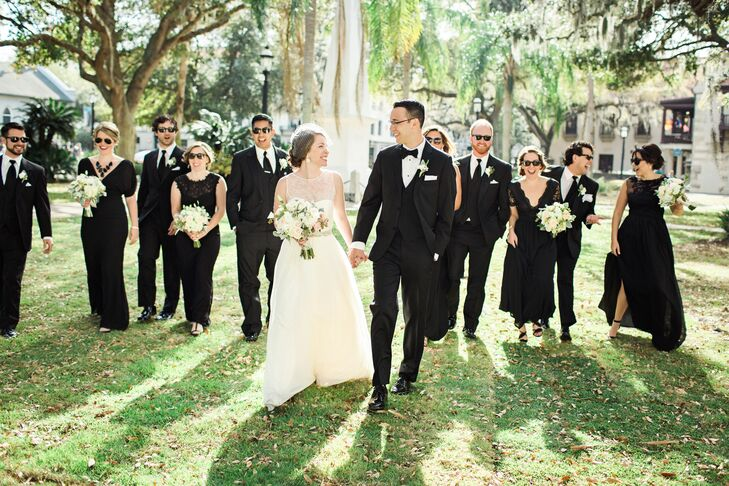 """""""We both wanted a classic look for our wedding,"""" says Alex. Bobby and his groomsmen donned classic black tuxedos for the wedding, which complemented each bridesmaid's different style black floor-length dress."""