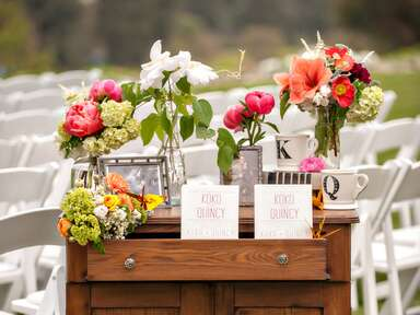 Outdoor wedding program table setup with family photos and flowers