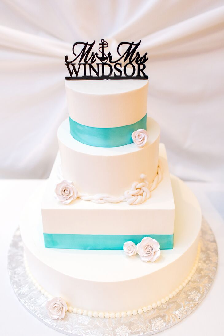 The white wedding cake had three round tiers and a square middle tier. The cake was decorated with white cake flowers and a fondant rope accent. It also featured turquoise ribbon accents and a nautical-themed cake topper.