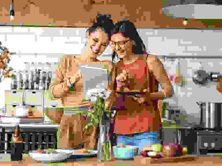 two women cooking and reading recipe in modern kitchen