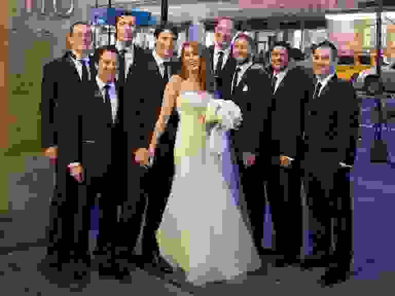 Bride poses with groomsmen at Manhattan wedding