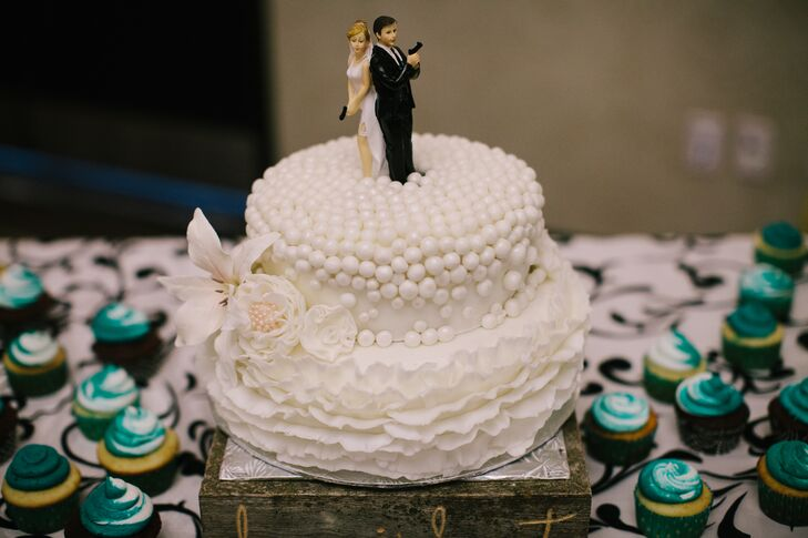 A custom cake topper of the bride and groom holding guns (since they're both police officers) stood atop a two-tier white cutting cake. The guests enjoyed delicious cupcakes.