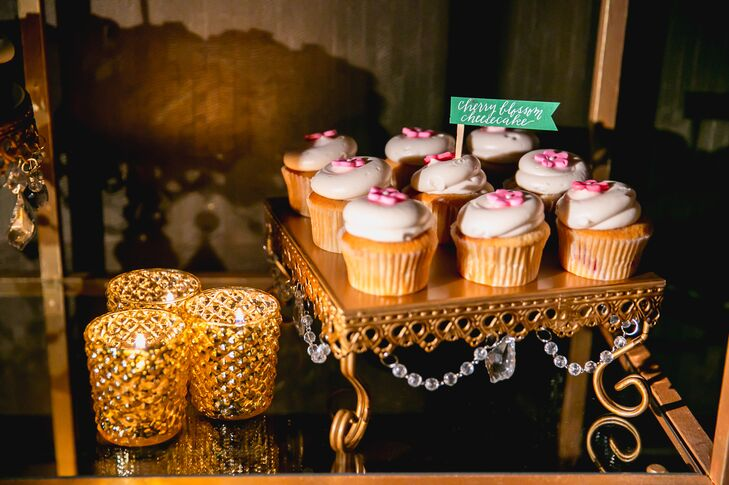 A gold elegant stand next to gold votive candles displayed cherry blossom cheesecake cupcakes made by Georgetown Cupcakes, among many other flavors served for dessert.