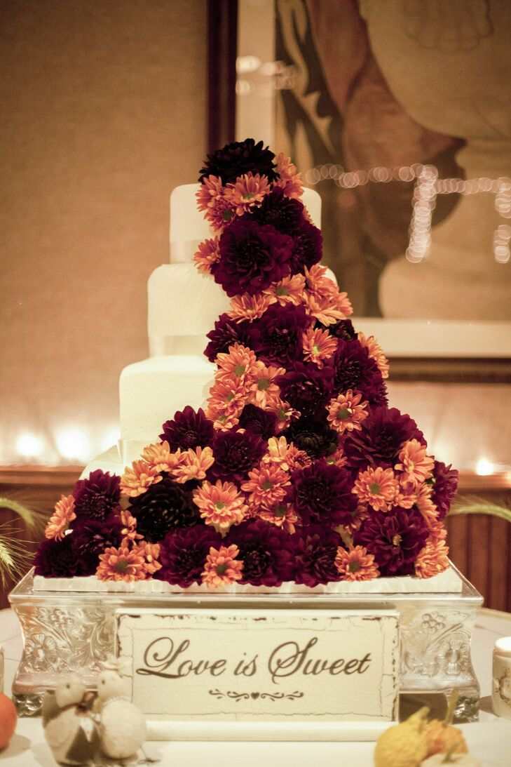 Caitlin and Mark's four-tiered round cake was decorated with a cascade of orange and red mums and cream-colored satin ribbon.