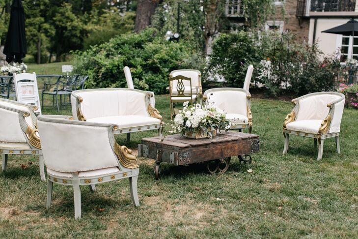 For the cocktail hour, the couple brought in rustic furniture like white chairs and reclaimed wood tables.