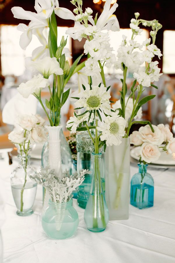 "The bride hand-dyed glass vases to look like vintage blue bottles. ""I decided that varying single white stems in beautiful vintage blue bottles would be the perfect way to showcase my simplistic vintage style while minimizing flower costs,"" the bride says."