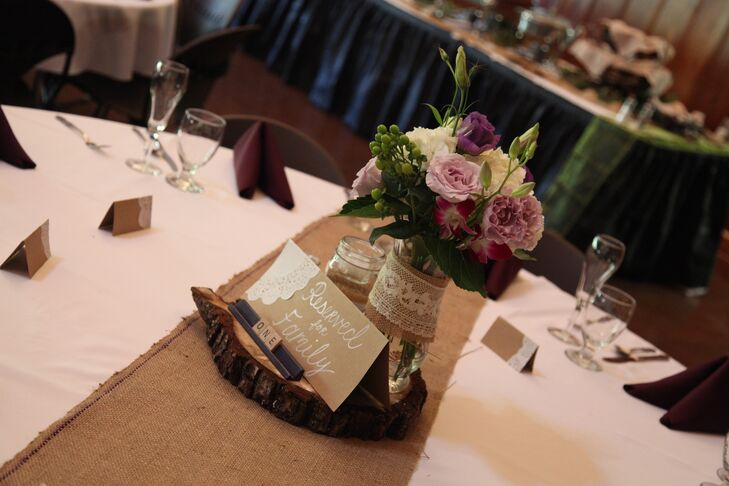 The couple opted for classic rustic centerpieces with bright floral blooms, burlap and lace-wrapped mason jars and wood slices. As a fun touch, the couple used Scrabble tiles for the table numbers.