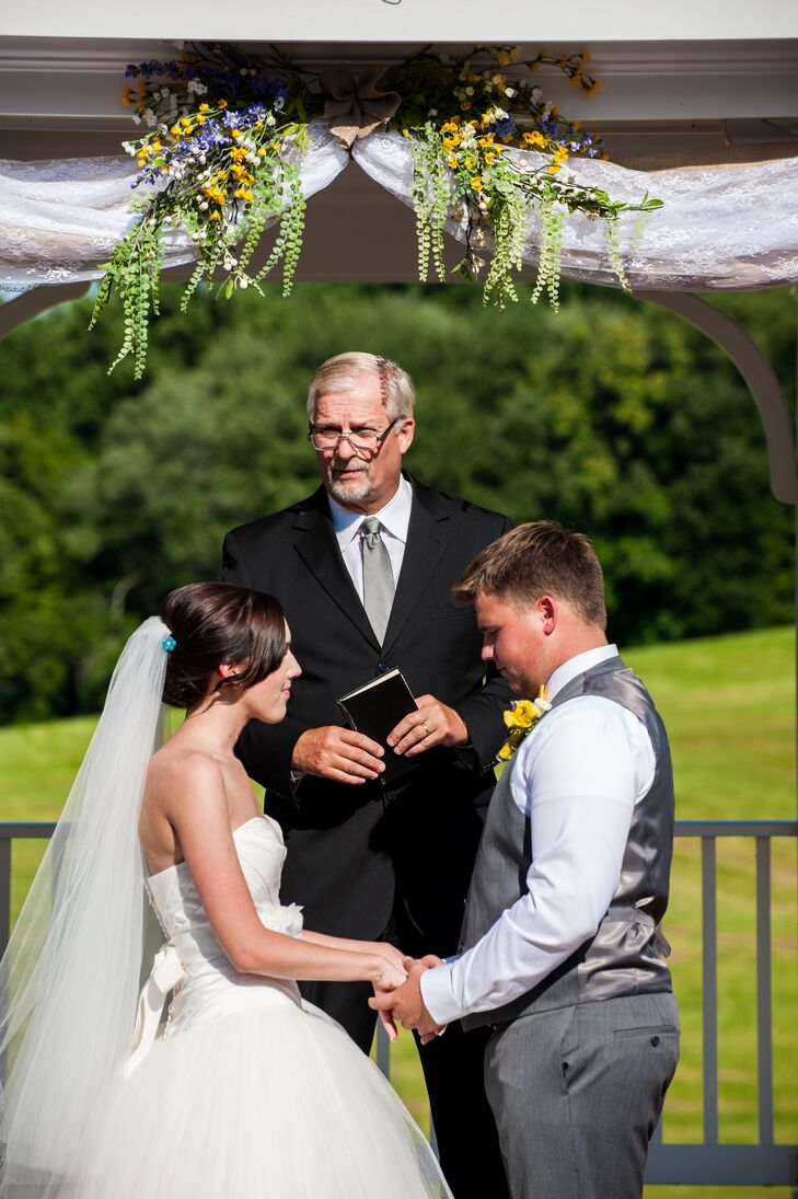Haley and Jeremiah held hands in matrimony as they stood under the pavilion, with wildflowers and greenery decorating the top. Jeremiah had a charcoal gray vest that matched his pants, with a canary yellow and white flower boutonniere pinned to his outfit.