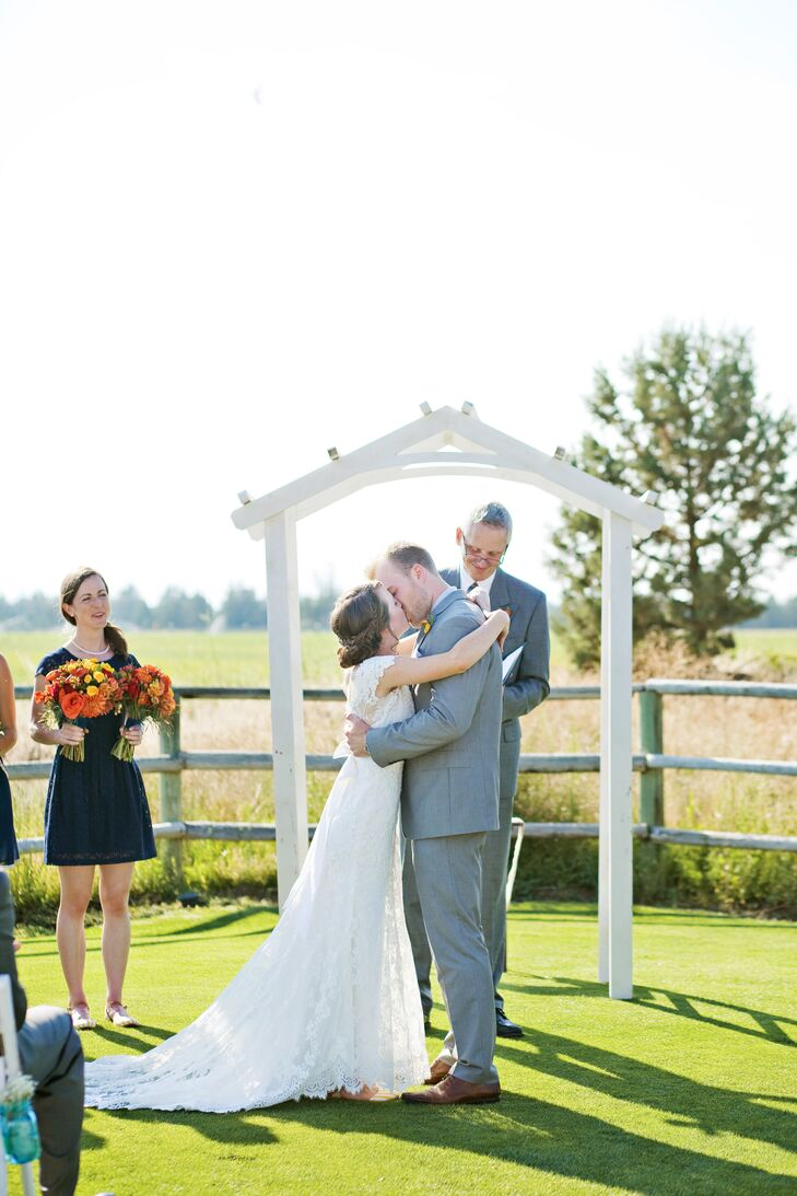 """Sara and Kris shared their first kiss in front of the simple white wedding arch, with a backdrop of the natural farmland. """"I think the moment that most defined us as a couple was the moment I turned the corner to walk down the aisle and caught Kris's eyes,"""" Sara says. """"He couldn't keep his tears in, and I can still remember the pure, vulnerable love I felt from him at that moment."""""""