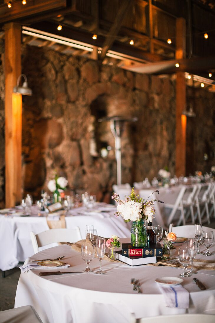At the barn reception, round tables were dressed in white tablecloths and decorated with book centerpieces with hydrangea and lavender arrangements.