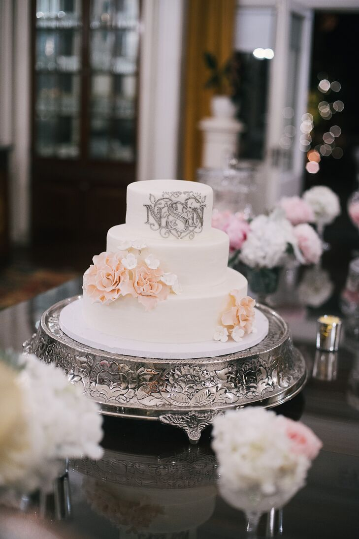 The three tier, white wedding cake was decorated with peach cake flowers and a silver monogram and displayed on a silver cake stand. The cake was flavored red velvet and spice.