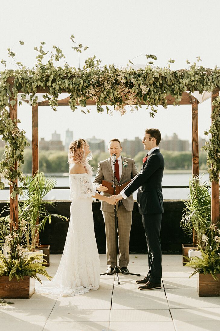 Couple Under Wood Chuppah with Tropical Greenery