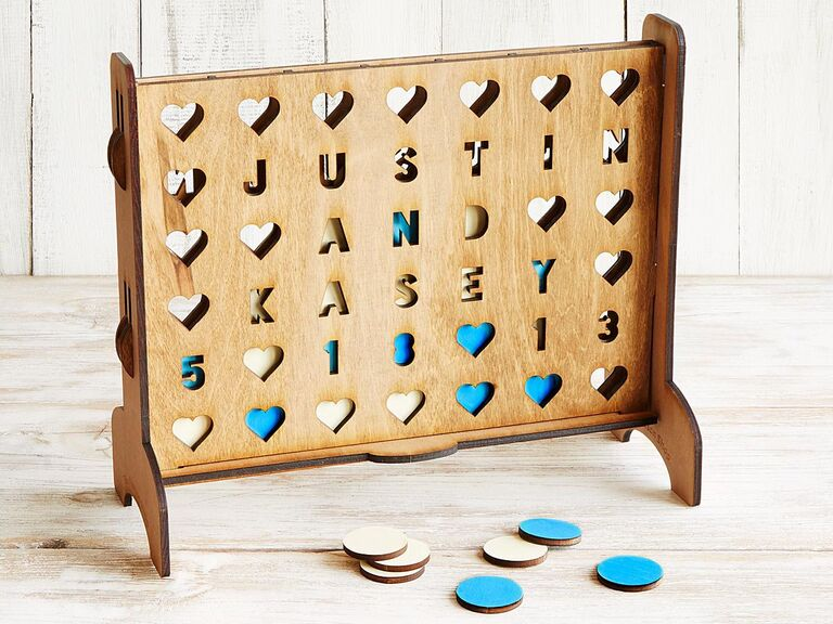Personalized wooden four across game with couple's names as the holes