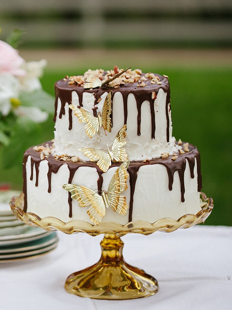 Whimsical wedding cake with a chocolate drip design and gold butterflies