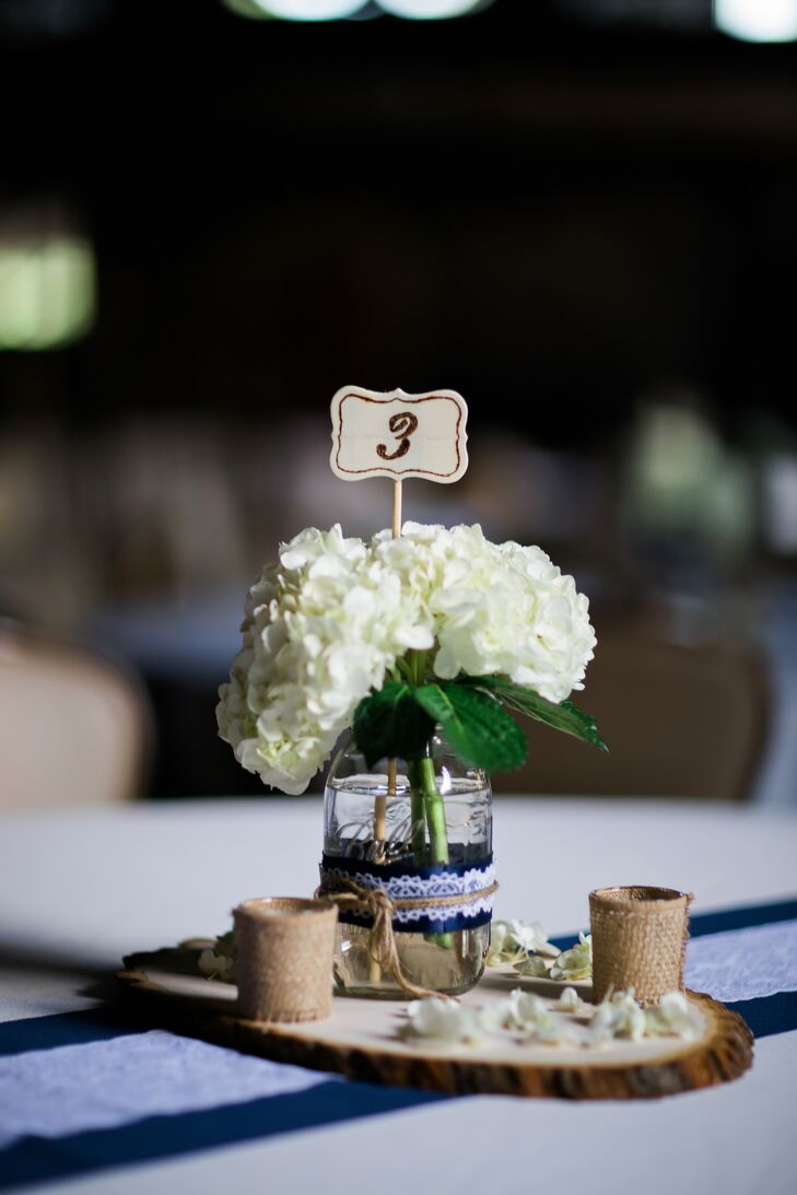 Wanting the decor to impart a relaxed, inviting feel to the day, Aubrey and Robert opted for accents and details with rustic flair. The couple chose a navy and white palette and looked to burlap, twine and wooden accents to infuse the day with a hint of laid-back country charm. For the centerpieces, each table was topped with a wooden round, on which a lace-wrapped mason jar filled with fluffy white hydrangeas, twine-wrapped candles and flower petals were arranged.