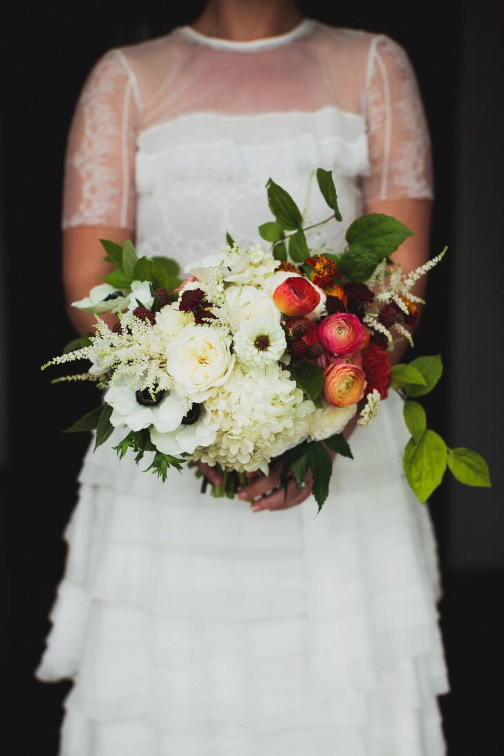 Helen held a bouquet of ivory anemones, peonies and hydrangeas mixed with red ranunculus.