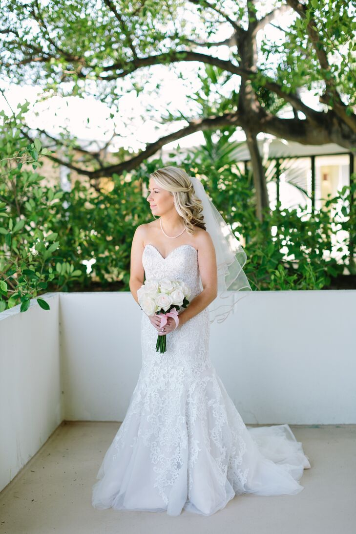 Laura chose a strapless Allure Romance champagne wedding dress with an ivory lace overlay and sweetheart neckline. The mermaid gown was accented with a pearl necklace and elbow-length veil.