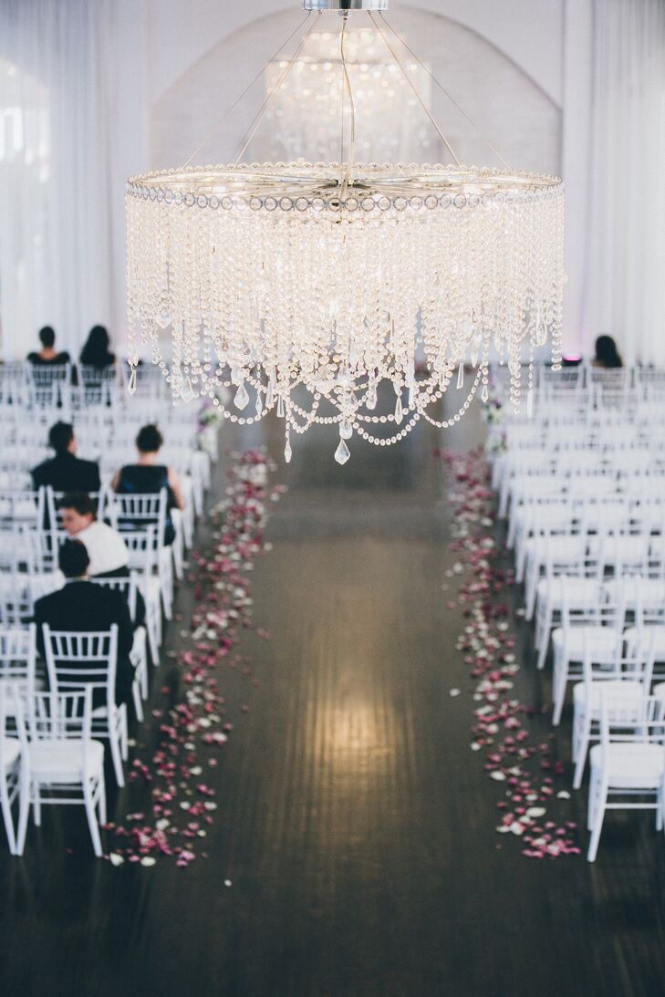 The all-white ceremony space was decorated with white chiavari chairs and rose petals.