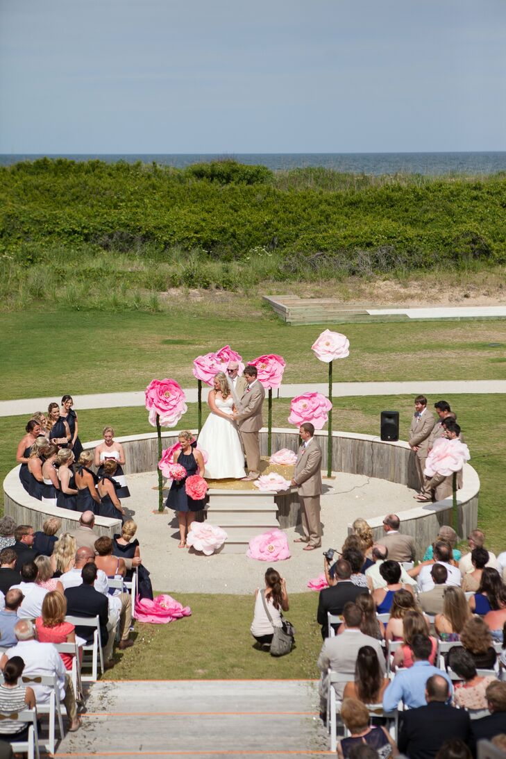 Katey and Matt covered a fire pit with a bright gold floor to stand on during their beachfront ceremony. They were surrounded by huge pink paper flowers made by Renee Landry for a unique look.