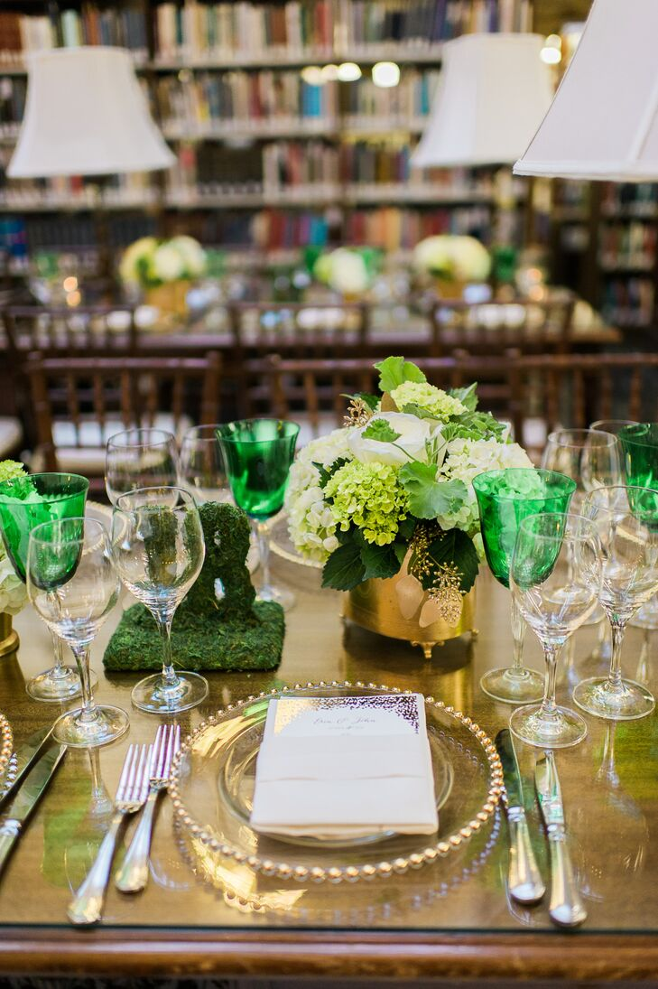 Dining tables were arranged with gold vases of hydrangeas and viburnum, gold-trim chargers and emerald green goblets. Table numbers were indicated with mossy block numbers.