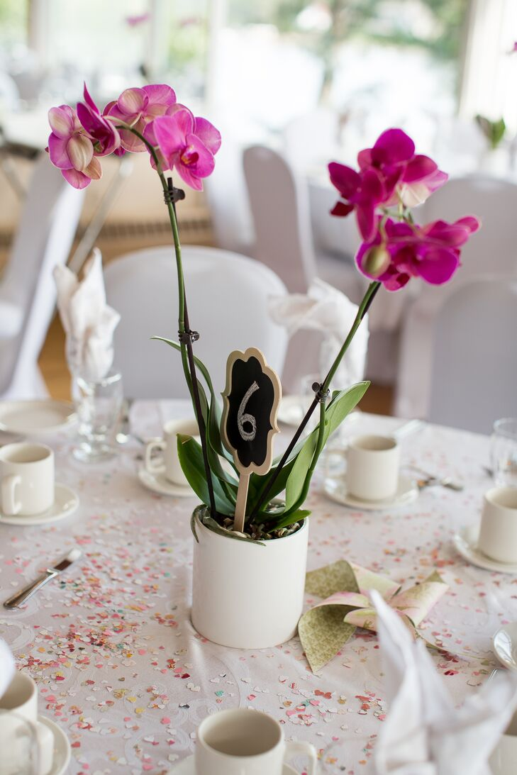 Each table had a blooming purple orchid as a centerpiece, a reference to the couple's personal orchid collection. The table numbers were tucked into each pot.
