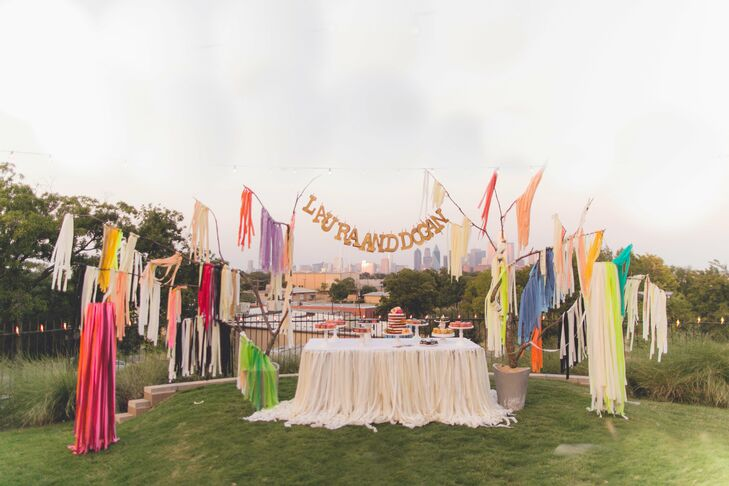 The cake and dessert table was surrounded by colorful paper fringe and had a large custom banner with the couple's names hanging across the top.