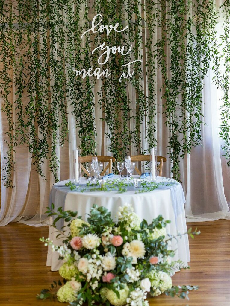 Sweetheart table at wedding reception with hanging greenery and lush floral arrangements