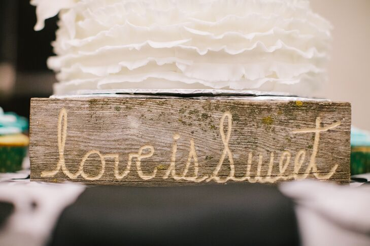 "A wooden, rustic 'Love is sweet"" sign was displayed in front of the cutting cake and cupcakes."