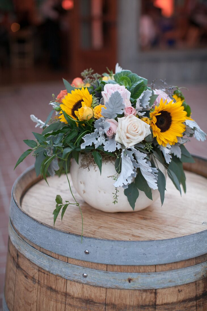 A flower arrangement filled with yellow sunflowers, pastel-colored roses and dusty miller mixed with greenery was positioned inside a white pumpkin. The arrangement was positioned on top of a wooden barrel.