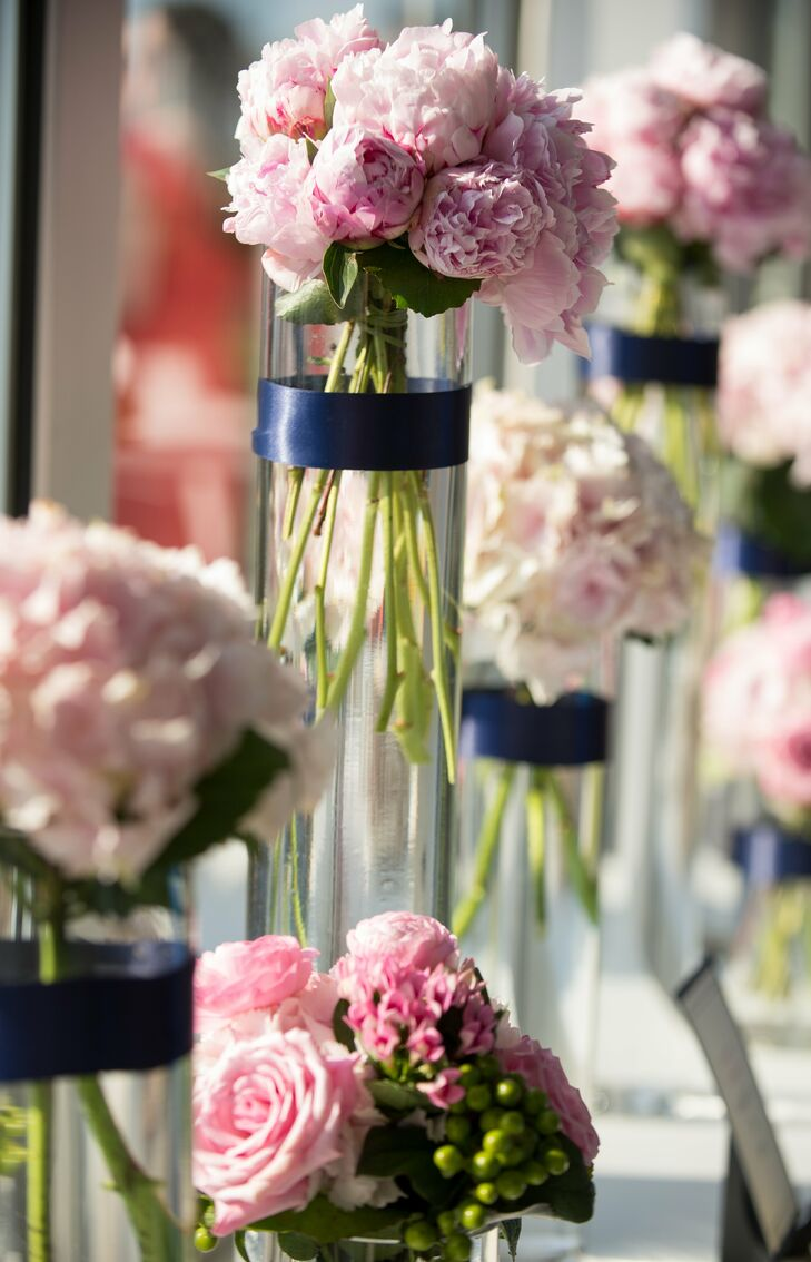 Bouquets of pink hydrangeas, peonies and garden roses were placed in clear vases with navy blue ribbon bands.