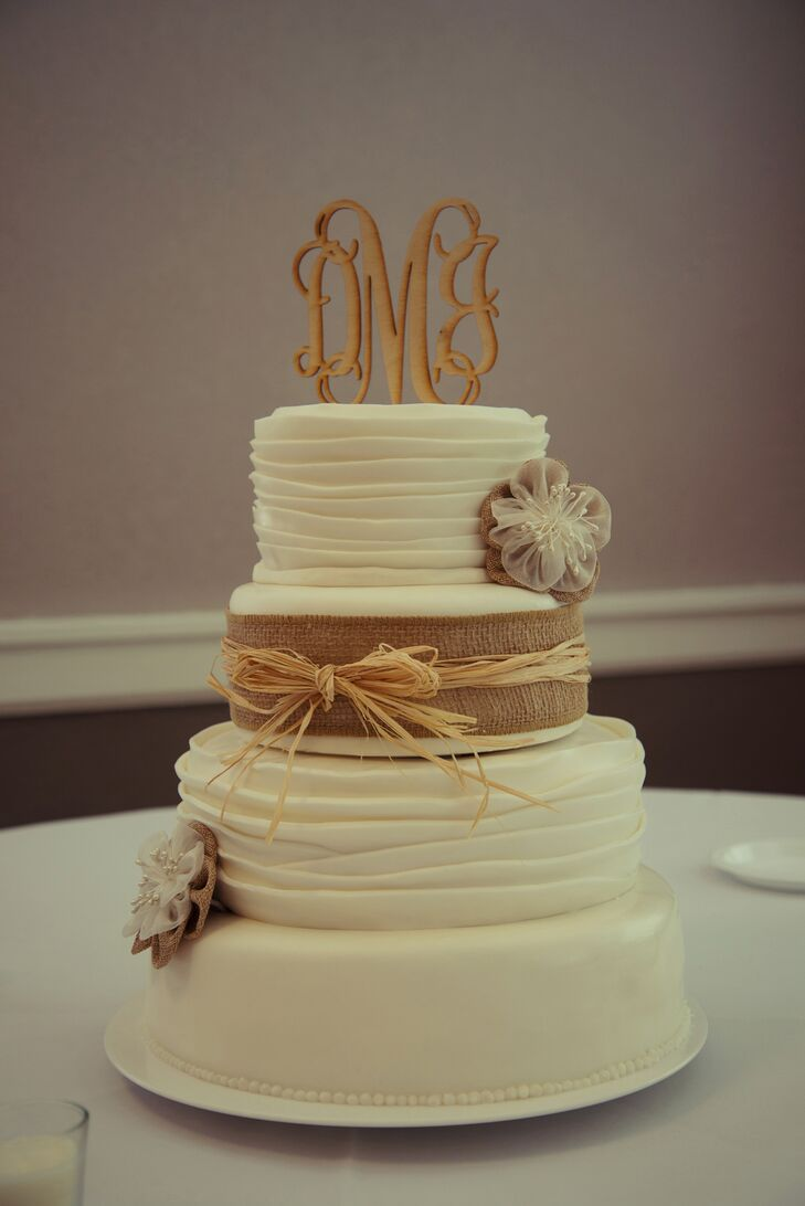 The four-tier lemon and buttercream wedding cake was wrapped in a ribbon of burlap with a straw bow decorated with small burlap and lace flowers. An elegant monogram cake topper was painted to resemble wood to fit in with the rustic theme.