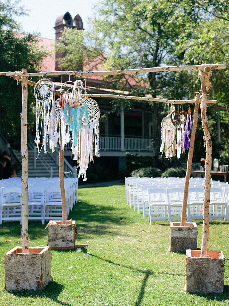 Simple wood arch with dream catcher decorations for an outdoor wedding
