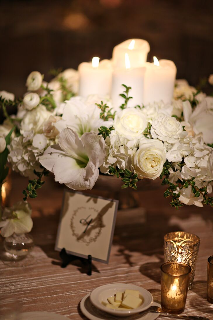 Flower arrangements made up of roses, ranunculus, hydrangeas and lilies filled silver pedestal vases with candles. As if that weren't romantic enough, the centerpieces were surrounded by votive candles for a complete candlelit glow.  These centerpieces looked pretty against the textured gold tablecloths on the dining tables.