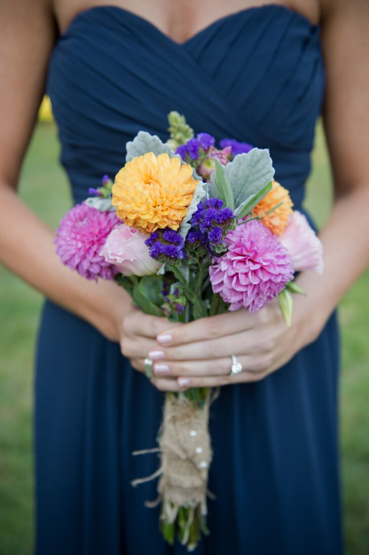 Bridesmaids carried smaller arrangements of pink and yellow-orange dahlias accented with clusters of deep purple flowers and soft dusty miller. Marguerite decided to use a local farmer instead of a traditional florist for all of the bouquets and arrangements.