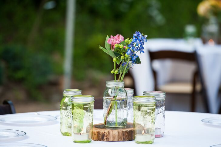 Jules and Scott wanted all the decorations to feel effortless and light. The reception tables were topped with slightly tinted mason jars, which the couple did themselves. The jars were filled with tea lights or wildflowers that felt like they blended into the rustic vineyard setting.