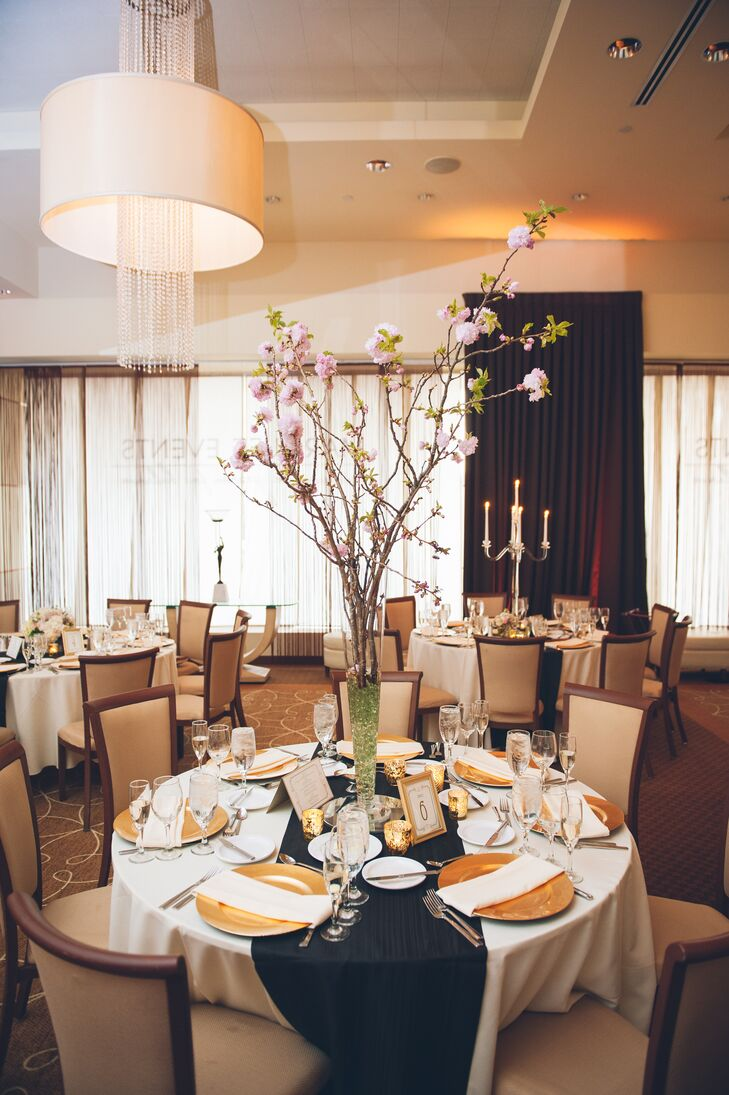 Pamela and Dan opted for not one but three centerpiece designs in their reception. Fleurescent, their florist, arranged the tallest with romantic cherry blossom branches. Green beading within its trumpet-style vase highlighted the display's leaves and natural design.