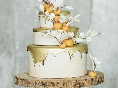 Metallic gold drip wedding cake with fondant peaches