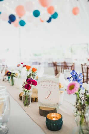 Neutral Tablescape with Colorful Blooms in Bud Vases and Wood Rounds