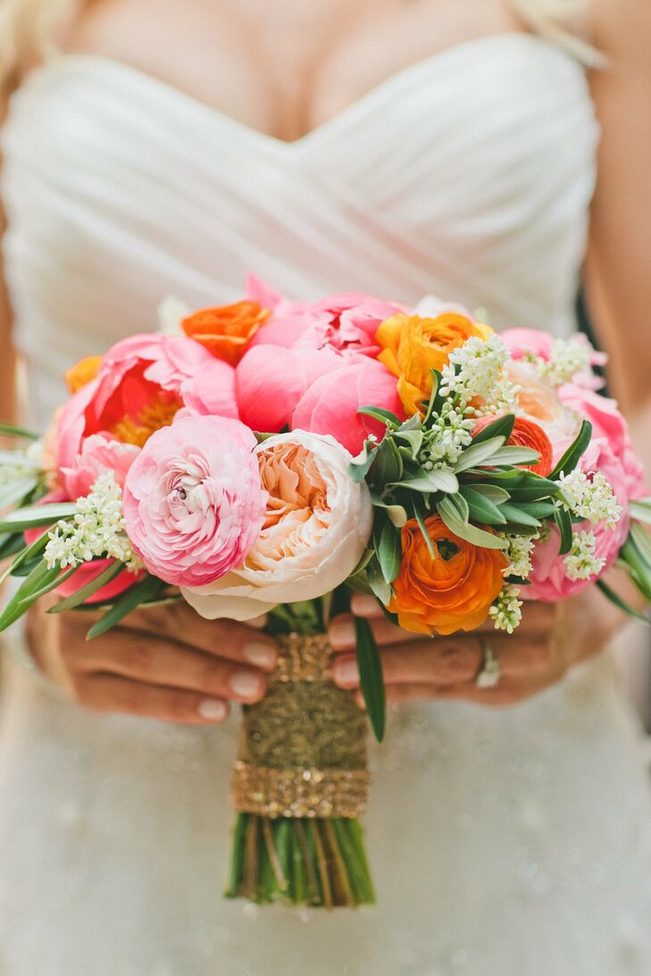Kendrick's bouquet mixed bright pink and orange ranunucluses, tulips and peonies with soft peach garden roses, delicate white lilac and olive leaves for a cheerful-yet-sophisticated look. The bouquet was wrapped with gold-sequined ribbon to tie into the glam theme of the day.