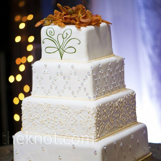 A different pattern decorated each of the four tiers of the couple's fondant cake, which was topped with orange orchids.