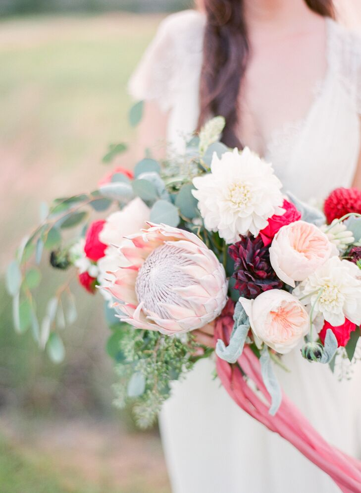 "Michelle carried a bouquet of white and red dahlias, seeded eucalyptus, blush garden roses, dusty miller and scabiosa pods down the aisle . A blush king protea stood out within the arrangement.  ""I knew I wanted a very large bouquet since my dress was simple,"" says Michelle."