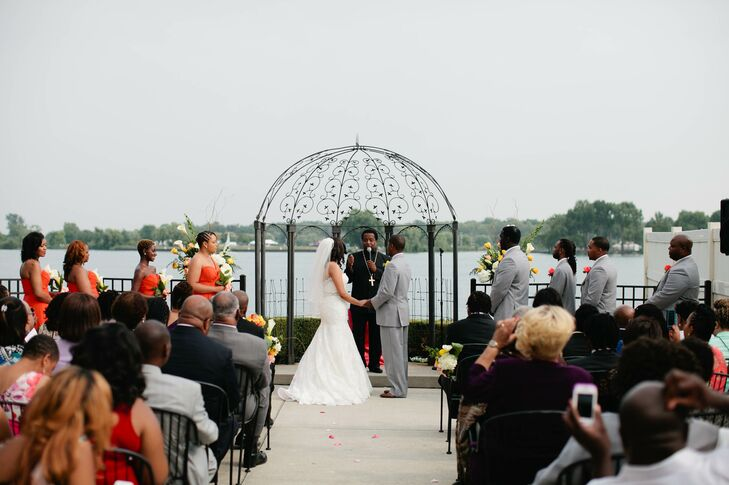 """""""The Roostertail captured the natural beauty of Detroit's riverfront and allowed our guests to enjoy the warm summer breeze,"""" Ebony says. """"The breathtaking view of the water painted a stunning backdrop for our day."""" Ebony and Jeremy used two arrangements of white calla lilies and yellow roses on either side of the metal arbor to highlight their picturesque venue. Each guest took in the view from rows of black metal chairs."""