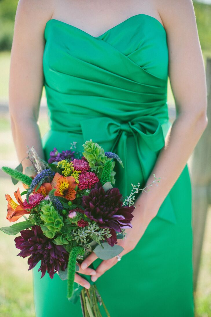 The bridesmaids carried textured bouquets of purple dahlias, green belles of Ireland, orange alstroemeria, yellow solidago and pink asters.