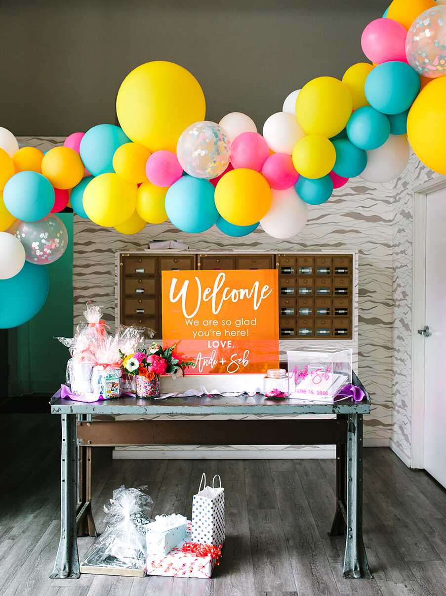 Bright yellow and teal blue balloon garland over a welcome table