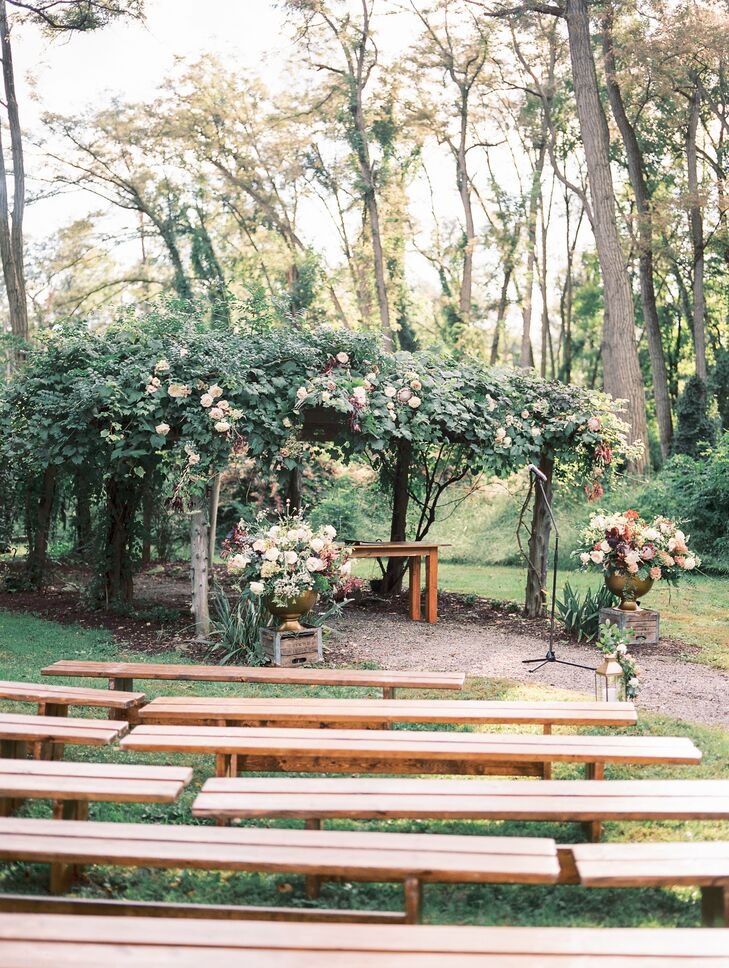 Rustic Ceremony Site with Benches, Flowers and Greenery Arch