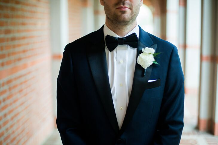 The groom wore a classic black tuxedo with a simple white ranunculus boutonniere.