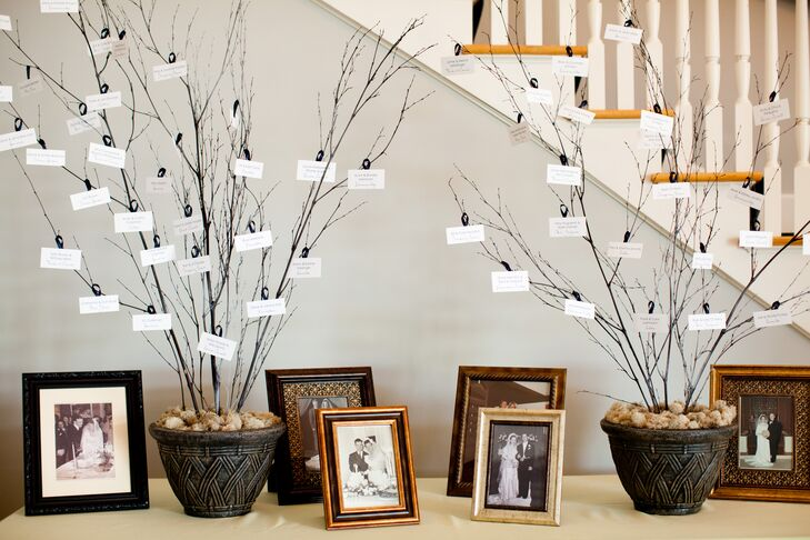 """I envisioned the escort cards hanging like leaves from branches on a tree which I created with pots, branches, and ribbon displayed alongside family photos,"" says Jackie."